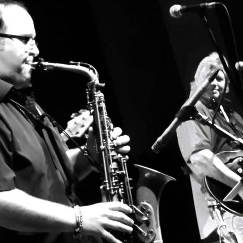 Black and white photo of Chris Beebe Aldridge playing sax with Climax Blues Band