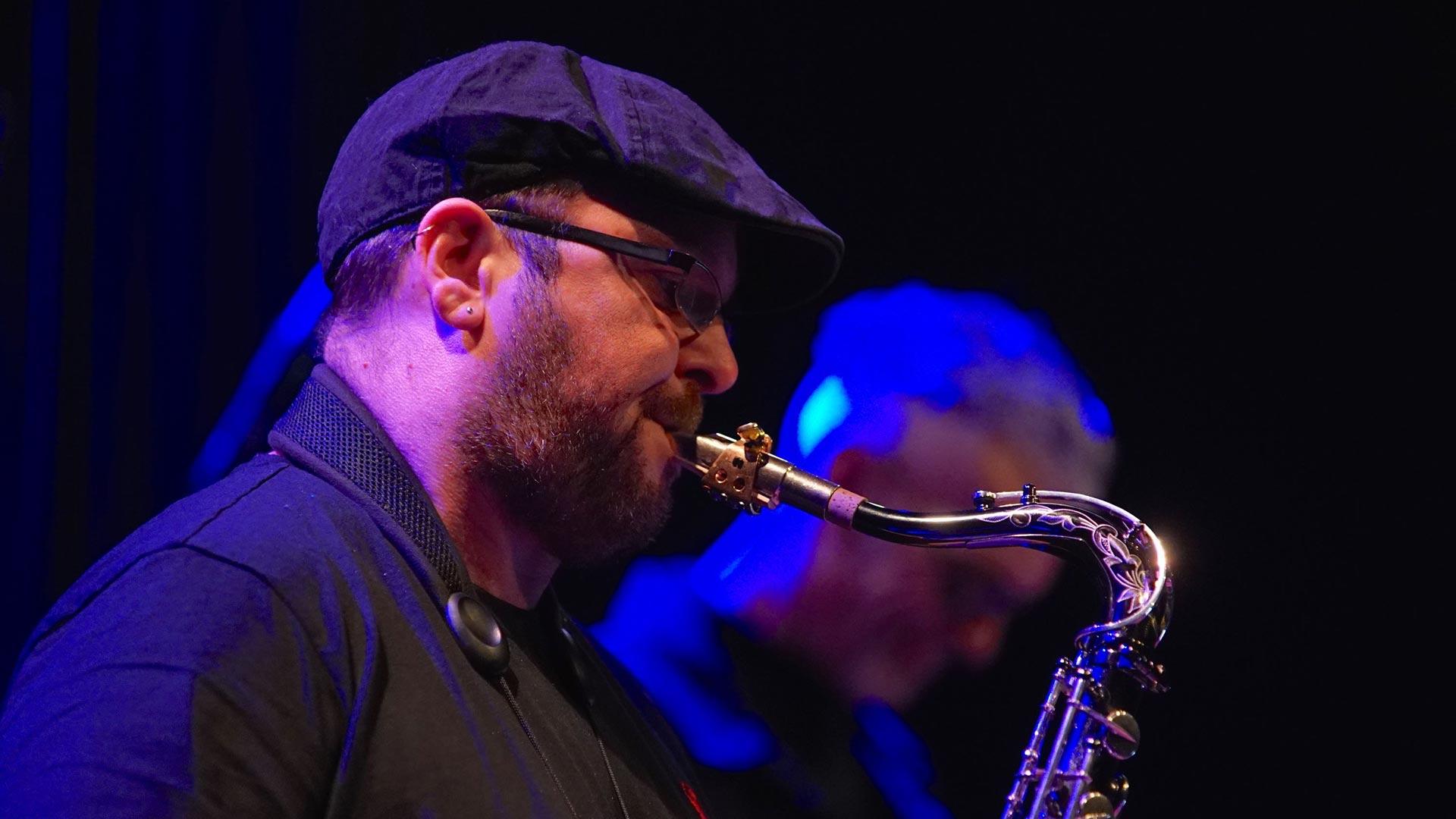Close up of Chris Aldridge playing sax wearing a flat cap