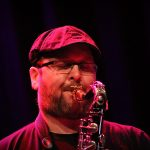 Chris Aldridge close up playing sax and wearing a flat cap