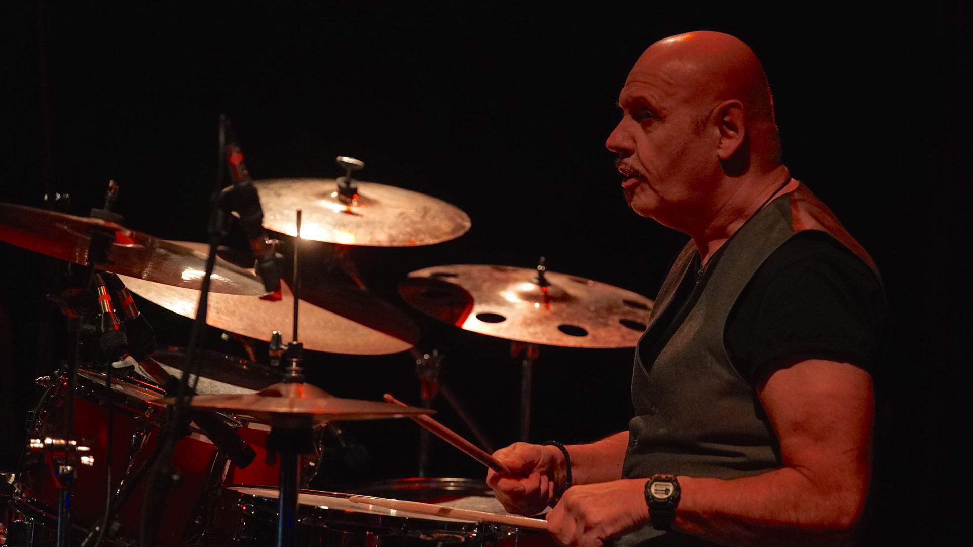 Roy Adams sits behind his red Yamaha drum kit and symbols