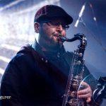 Chris Aldridge wearing a flat cap plays sax at HRH Blues Festival Sheffield UK 2019